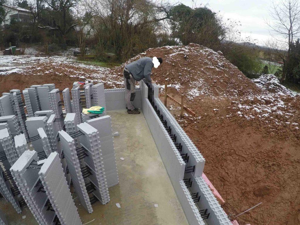 Die Ecken werden versetzt verzahnt angelegt genauso wie bei herkömmlichem Mauerwerk nur eben viel schneller...