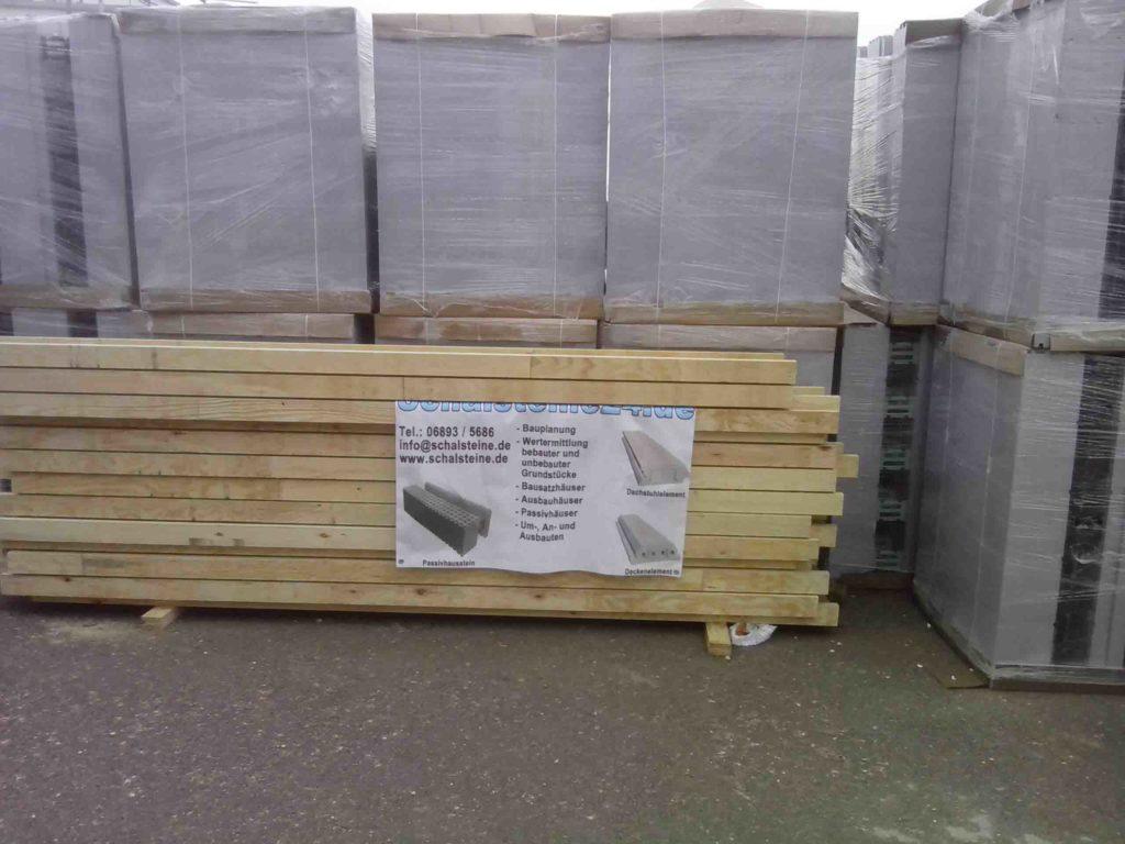 Eingeschweißte Paletten mit Passivhausschalsteinen an einer Baustelle