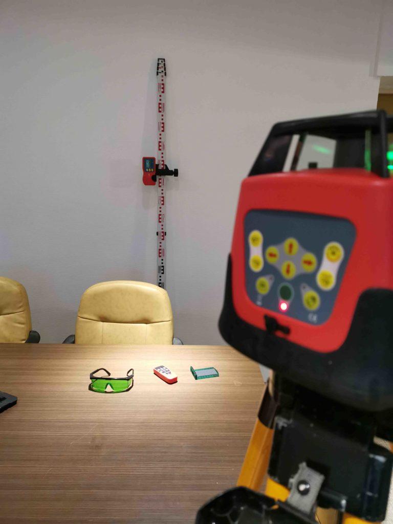 Lasernivelliergerät grün mit Empfänger auf Holzstativ