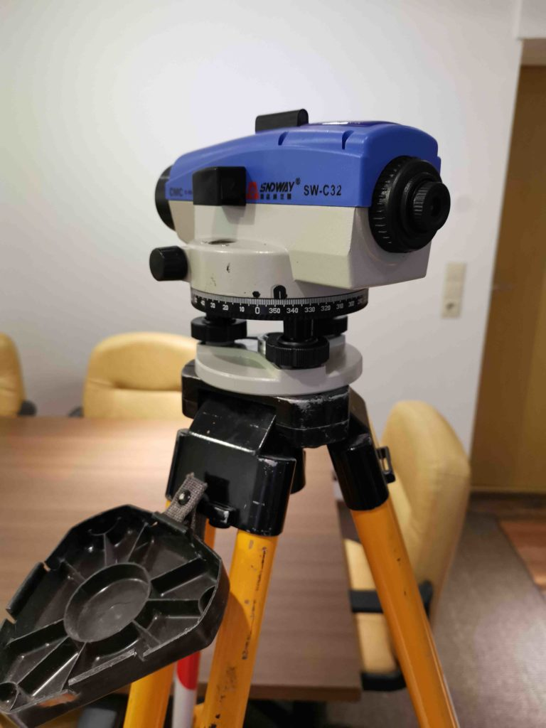 Optisches-Nivelliergerät 32 auf Holzstativ.